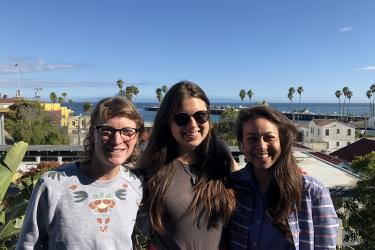 From left to right: Chessa, Madison, and LuLing in front of a view of the Santa Cruz wharf